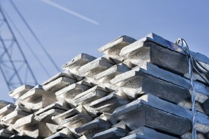 Shiny aluminum ingots with a crane in the background while a plane is flying over
